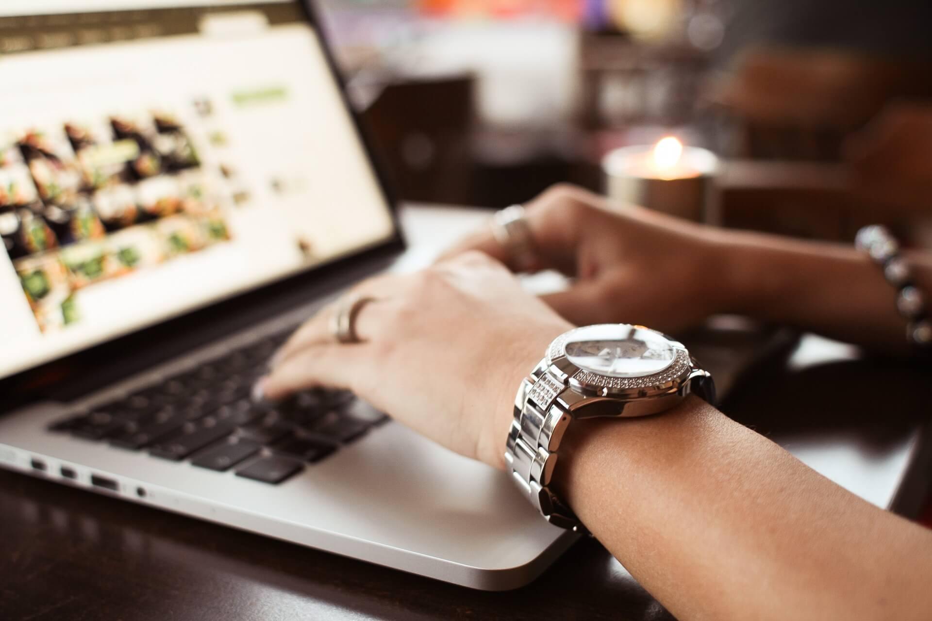 金属製の腕時計をする女性