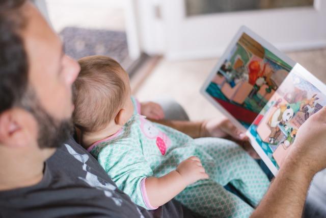 出産祝いのプレゼントを貰って喜ぶ赤ちゃんとパパを見つめるママ