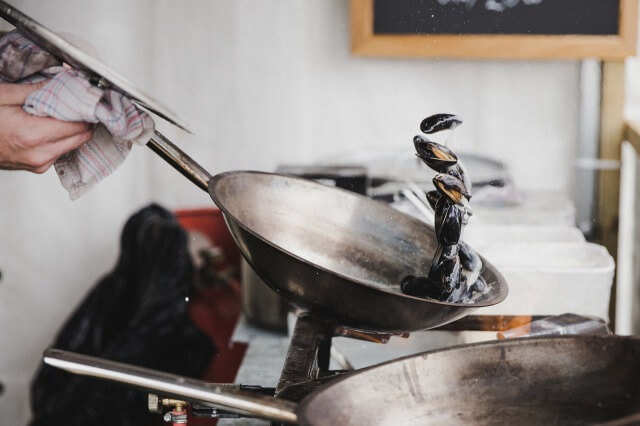 フライパンで料理をしている人
