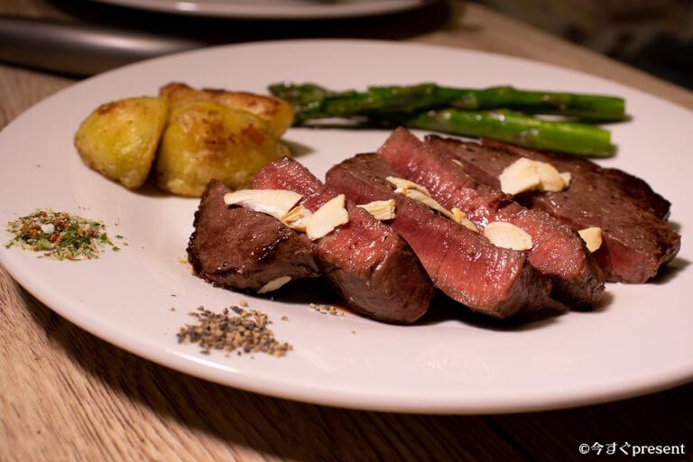 松阪牛やまと_コモモステーキ_お皿に盛り付けた写真_岩塩やガーリックスライスをのせた写真