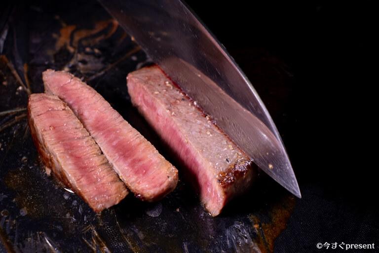 松阪牛やまと_コモモステーキ_包丁で切っている写真