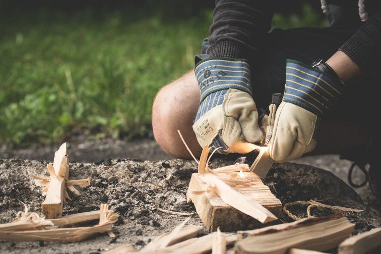 キャンプで道具を使って火をおこすイメージ
